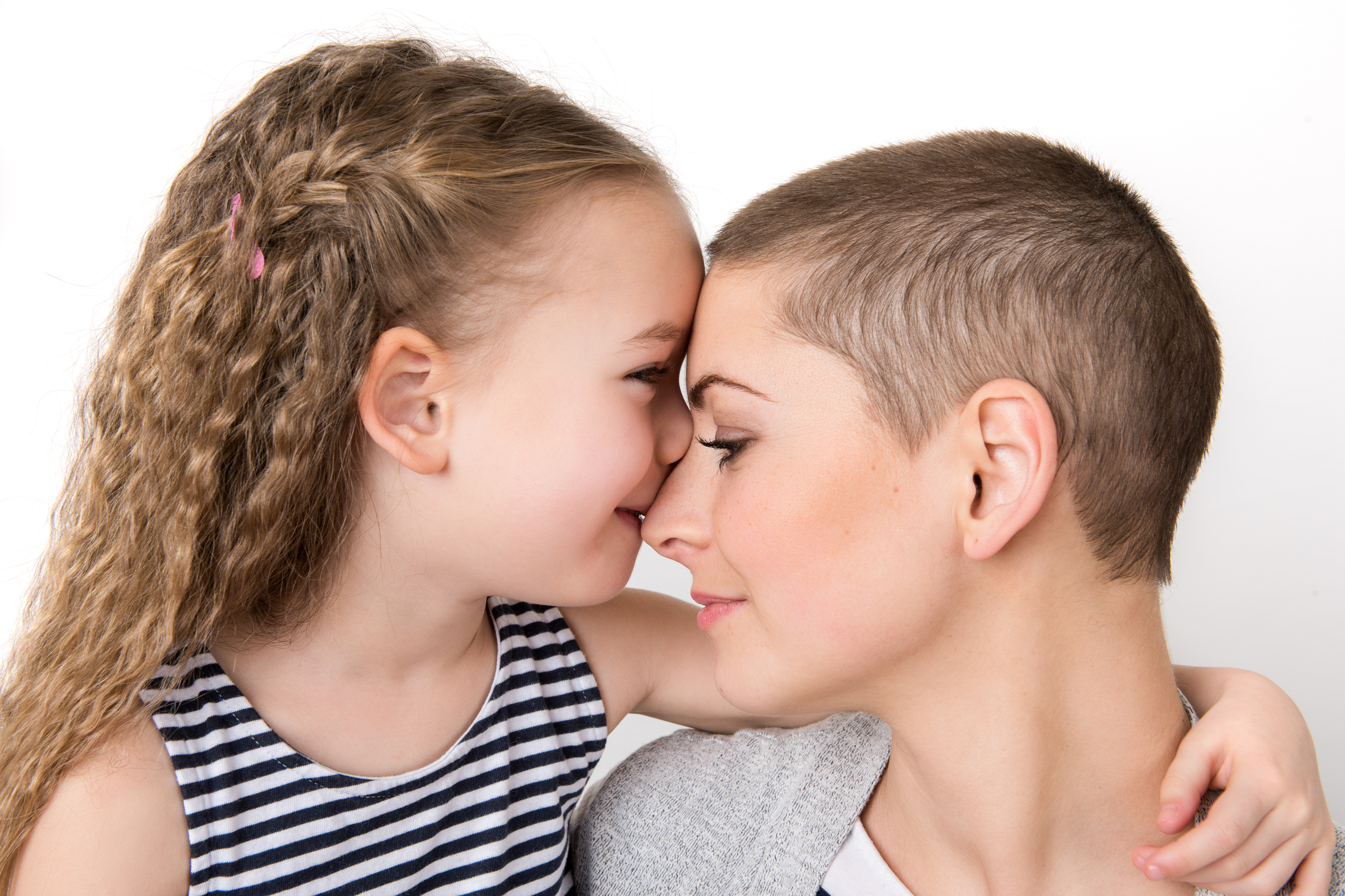 Cute preschool age girl with her mother, young cancer patient in remission. Cancer patient and family support concept.